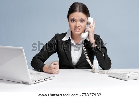 Casual angry business woman in office working with white table, laptop and talking by phone. Strict! - stock photo