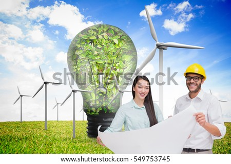 Casual architecture team working together at desk against wind turbines and bulb full of leaves