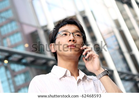 casual asian businessman talking on his cell phone. - stock photo