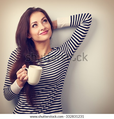 Casual attractive thinking woman holding cup of tea and pensive looking up. Vintage portrait - stock photo