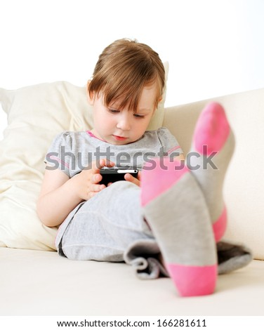 Casual baby sitting on a couch at home playing and touching a mobile phone