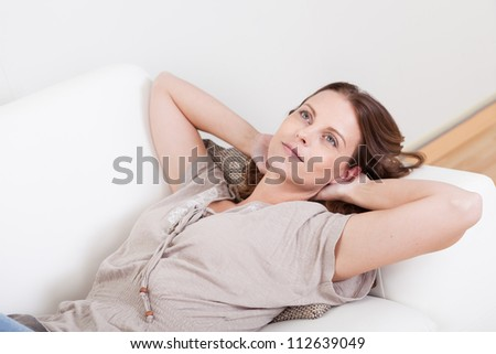 Casual barefoot woman in jeans lying on a couch in her living room with a cheerful smile - stock photo