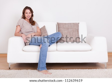 Casual barefoot woman in jeans sitting on a couch in her living room with a cheerful smile - stock photo