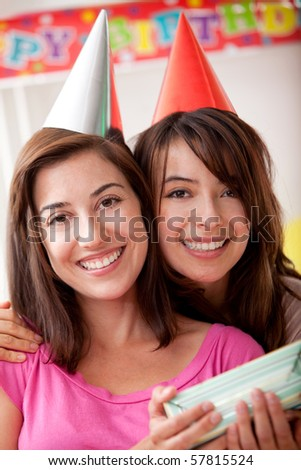 Casual beautiful friends smiling and holding a gift in a birthday party - stock photo
