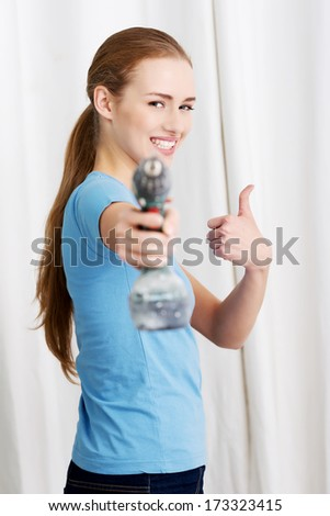 Casual beautiful house wife holding drill. Indoor background.
