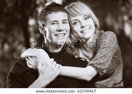 Casual beautiful young couple relaxing and cuddling in the park