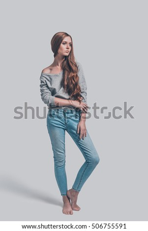 Casual beauty. Full length of attractive young woman in casual wear posing against grey background