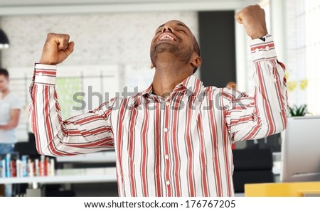 Casual black man celebrating success at office, arms raised. - stock photo