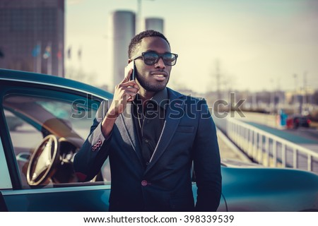 Casual black man in a suit talking by smartphone near a car. - stock photo