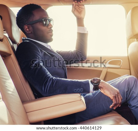 Casual black man in sunglasses sitting in a car. - stock photo