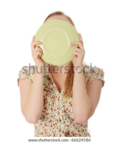 Casual blond woman licking plate - stock photo