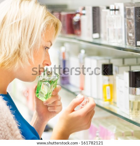 Casual blond young woman smelling perfume in retail store. - stock photo