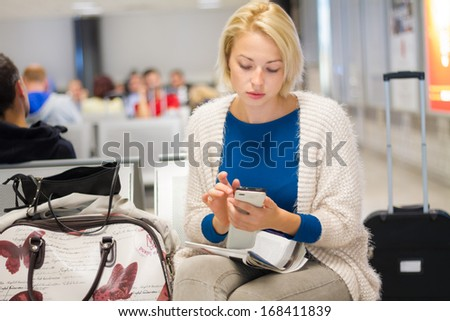 Casual blond young woman using her cell phone while waiting to board a plane at the departure gates. - stock photo