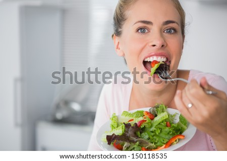 Casual blonde posing while eating salad and holding a mixed salad dish - stock photo