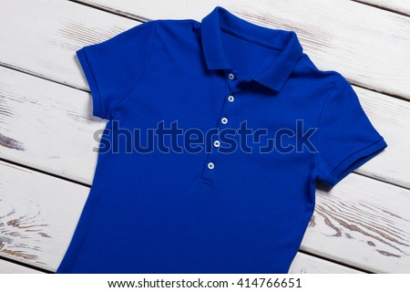 Casual blue polo t-shirt. T-shirt on white wooden background. Basic t-shirt on store shelf. Last item sold at discount. - stock photo