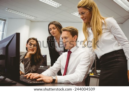 Casual boss showing something to his business team in the office