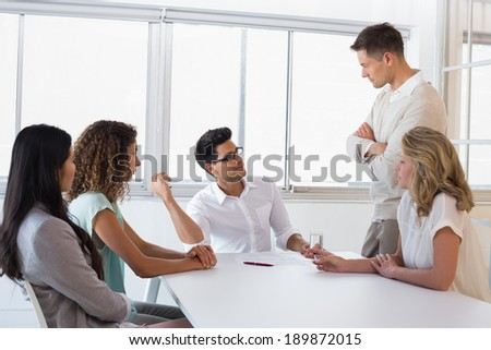 Casual boss standing over his employee looking angry in the office - stock photo