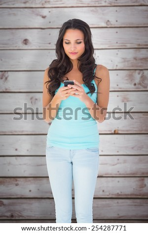 Casual brunette sending a text against wooden planks - stock photo