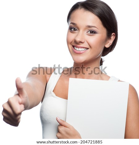 casual brunette young woman in white singlet holding sign and showing thumbs up isolated on white