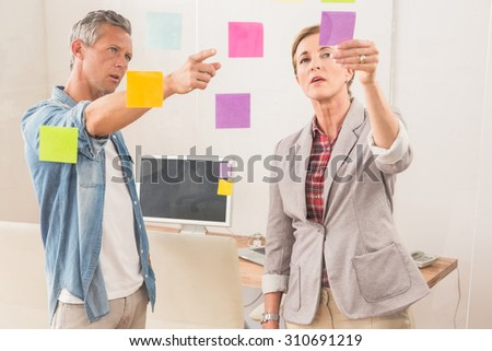 Casual business colleagues working with sticky notes in the office - stock photo