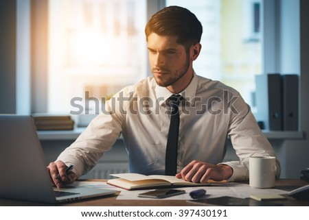 Casual business day. Pensive young handsome man using his laptop while sitting at his working place - stock photo