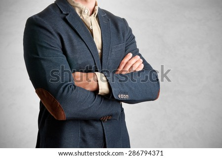 Casual business man with arms crossed in a grey background - stock photo
