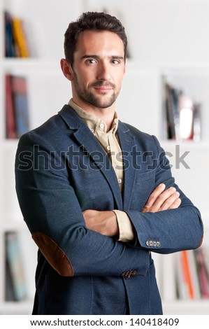 Casual business man with arms crossed with a bookshelf behind him - stock photo