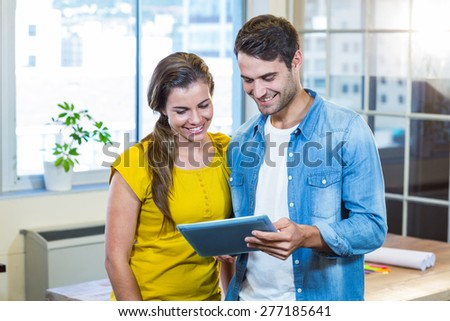 Casual business partners looking at tablet in the office - stock photo