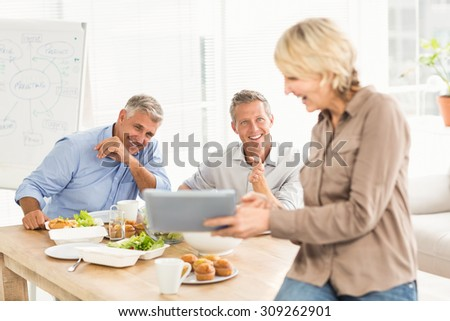 Casual business people looking at camera in office - stock photo