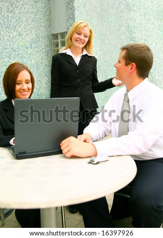 casual business people outdoor. one woman using laptop and two other having a chat
