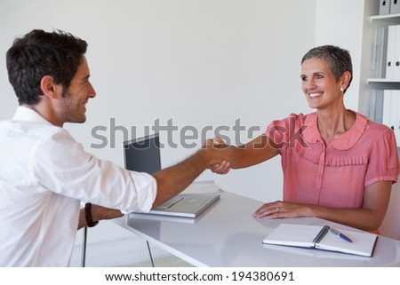Casual business people shaking hands at desk in the office - stock photo