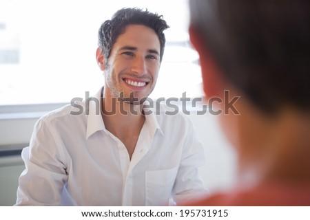 Casual business people talking at desk and smiling in the office - stock photo