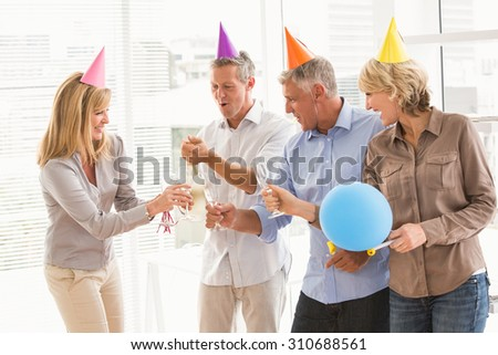 Casual business people toasting and celebrating birthday in the office - stock photo