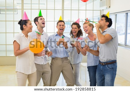 Casual business team celebrating with champagne and party poppers in the office - stock photo
