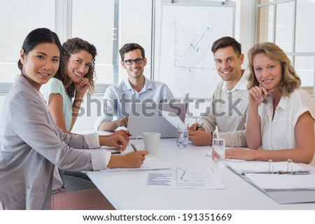 Casual business team having a meeting smiling at camera in the office - stock photo
