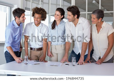 Casual business team having a meeting standing in the office - stock photo