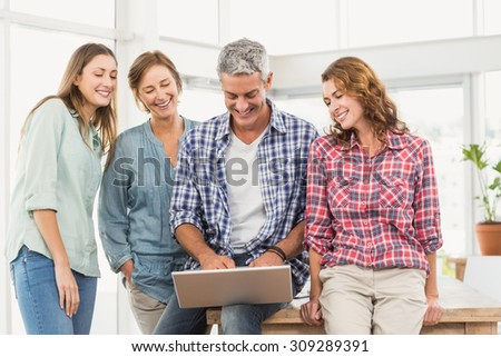 Casual business team having a meeting using laptop in creative office