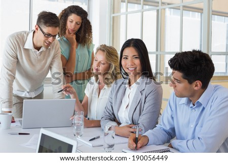 Casual business team having a meeting using laptop in the office