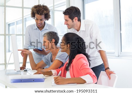 Casual business team having a meeting with computer in the office - stock photo