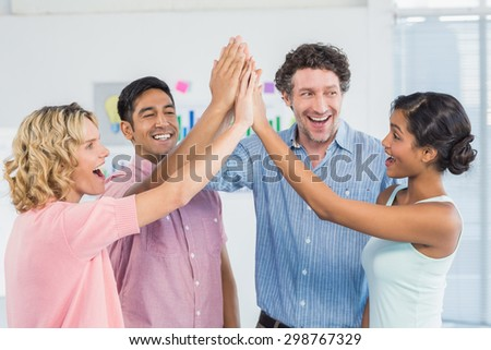 Casual business team high fiving in the office - stock photo