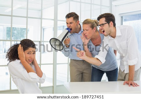 Casual business team shouting at a colleague in the office - stock photo