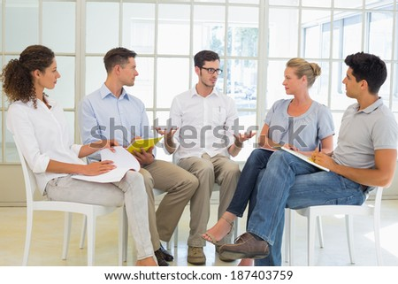 Casual Business Team Sitting In A Circle Having A Meeting In The