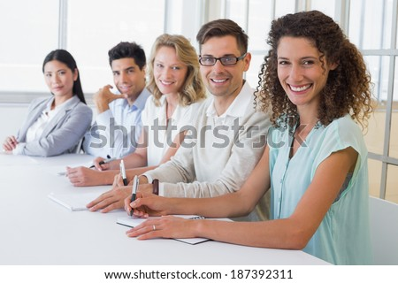 Casual business team smiling at camera sitting at desk in the office - stock photo