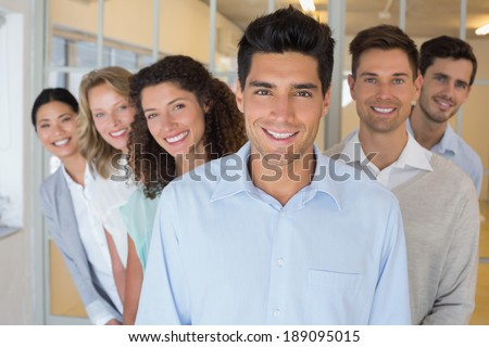 Casual business team smiling at camera together in the office - stock photo