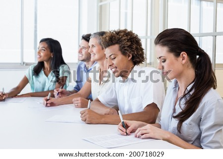 Casual business team taking notes in meeting in the office