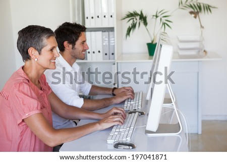 Casual business team working at desk using computers in the office - stock photo