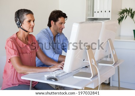 Casual business team working at desk using computers with woman using headset in the office