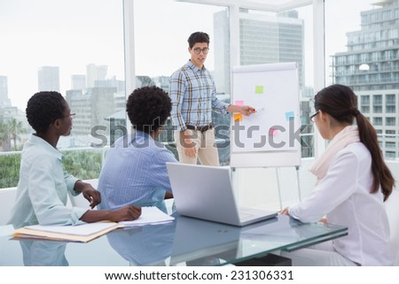 Casual business team working together at desk in creative office - stock photo
