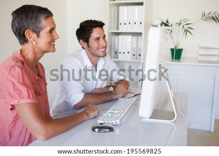 Casual business team working together at desk using computer in the office - stock photo