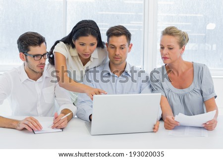 Casual business team working together at desk using laptop in the office - stock photo